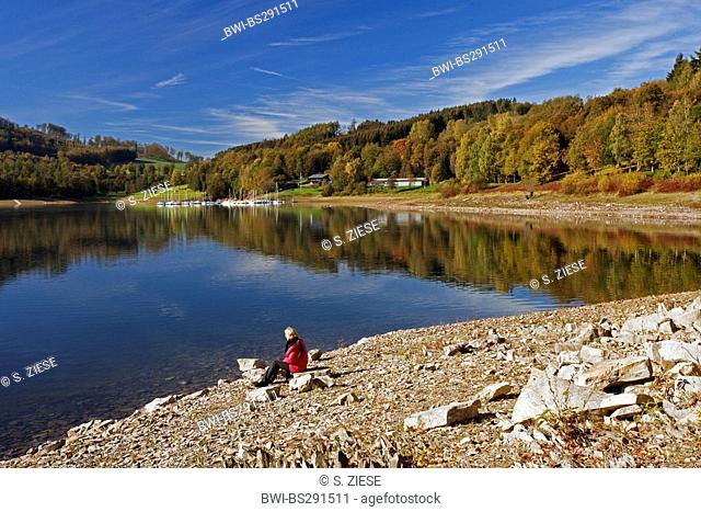 woman sitting at the lakefront of Henne storage lake and enjoying a good view, Germany, North Rhine-Westphalia, Sauerland, Meschede