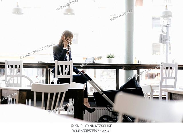 Businesswoman working from cafe with pram on her side
