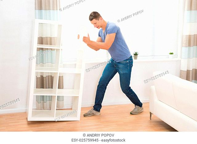 Young Man Moving Shelf In Living Room