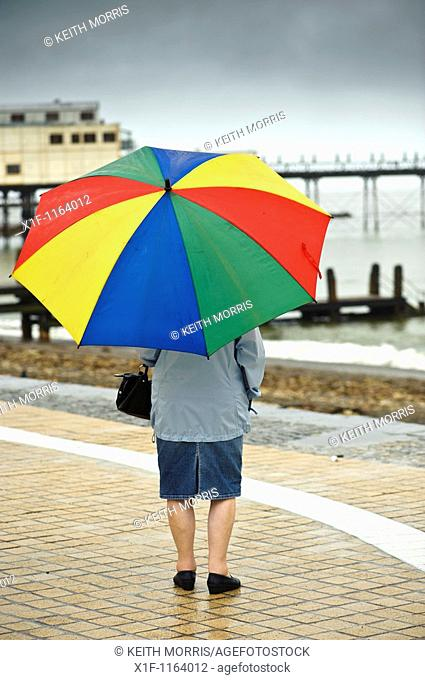Rear view of a woman sheltering under an umbrella on Aberystwyth promenade in the rain july wet summer afternoon, Wales UK