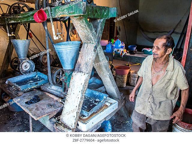 Salvadoran man work at a Corn tortilla dough factory in Suchitoto El Salvador. Corn has been a staple food in Central American cultures since pre-Columbian...