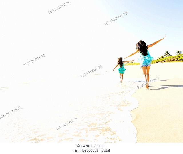Rear view of girl (6-7) and her mom running on beach