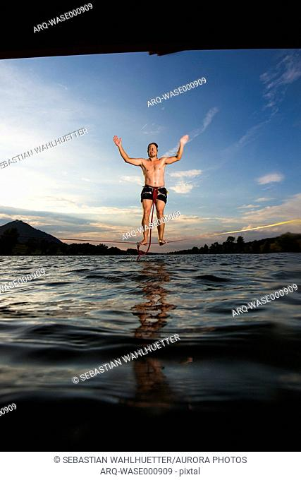 Front view of man jumping on slack line above lake, Vienna, Austria