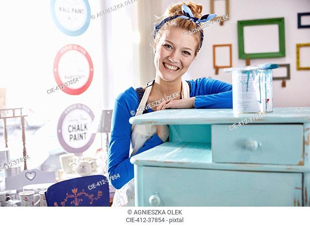 Portrait smiling, confident female artist painting side table blue in art class workshop
