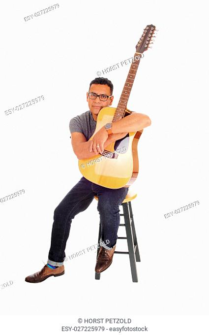 A middle age Hispanic man sitting on a chair, isolated for white .background, hugging his guitar, looking into the camera.