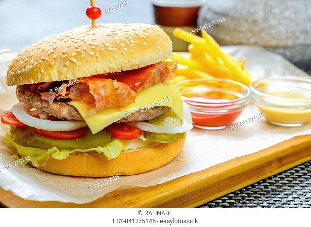 Cheese burger with bakon garnished with sauces and french fries