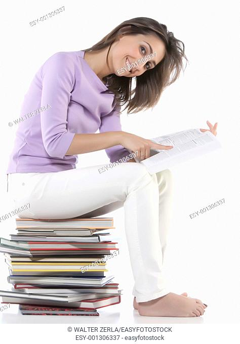 Smiling woman sitting on stack of books