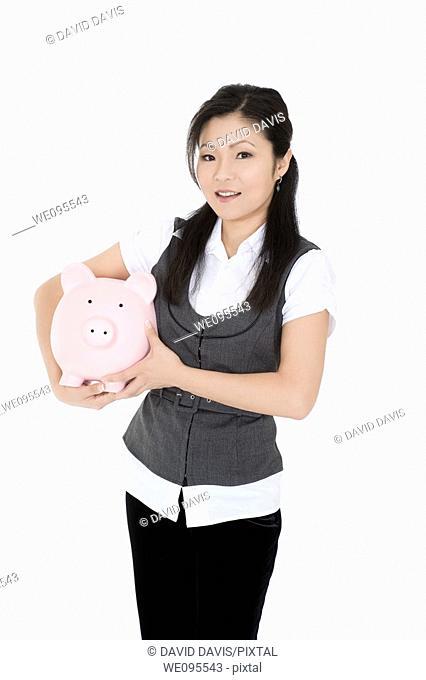 Beautiful Asian businesswoman holding a piggy bank