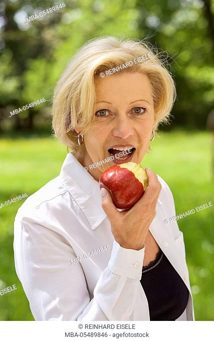 Woman bites in an apple