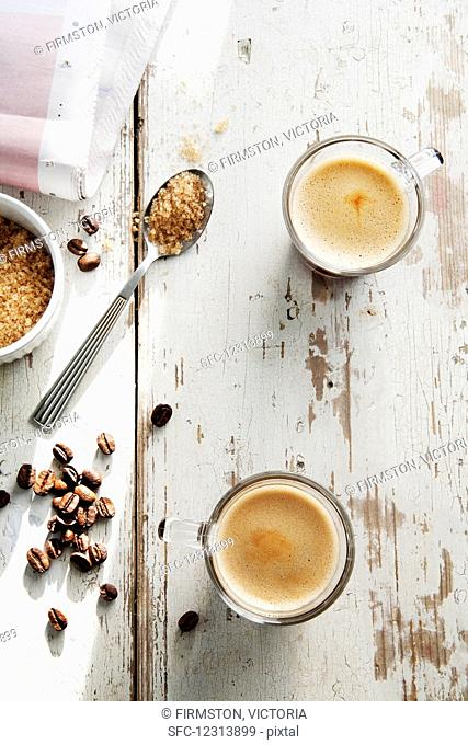 Coffee beans, a teaspoon of brown sugar and two cups of espresso on a whitewashed tabletop
