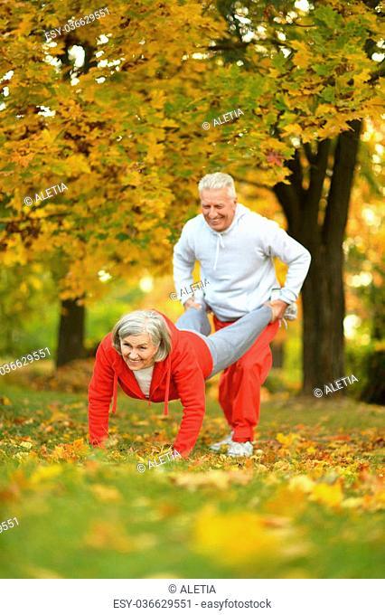 Happy fit senior couple exercising in autumn park