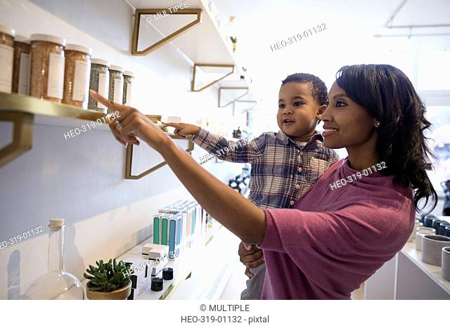 Mother and son browsing merchandise on shelf in shop