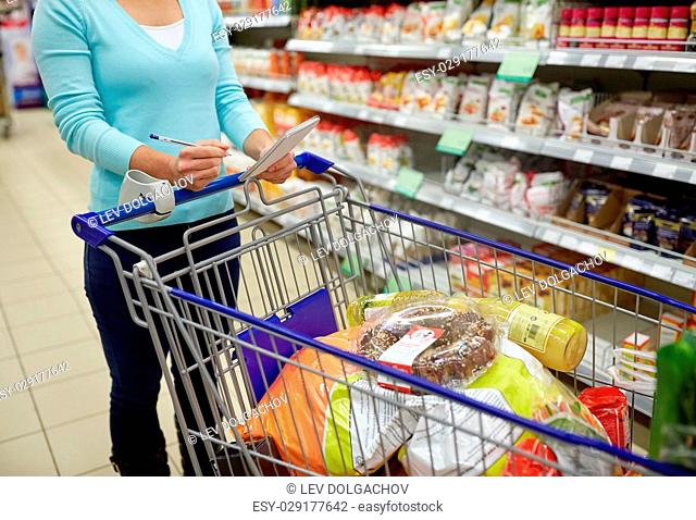 consumerism and people concept - woman with notebook and shopping cart or trolley buying food at grocery store or supermarket