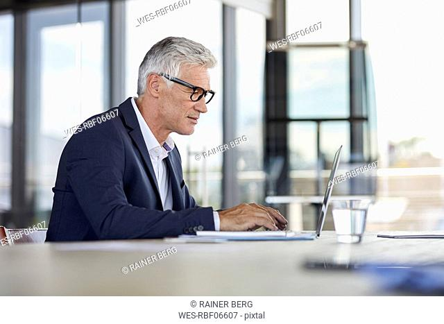 Businessman working in office, using laptop