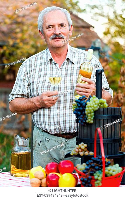 Happy elderly man with wine and harvest crops