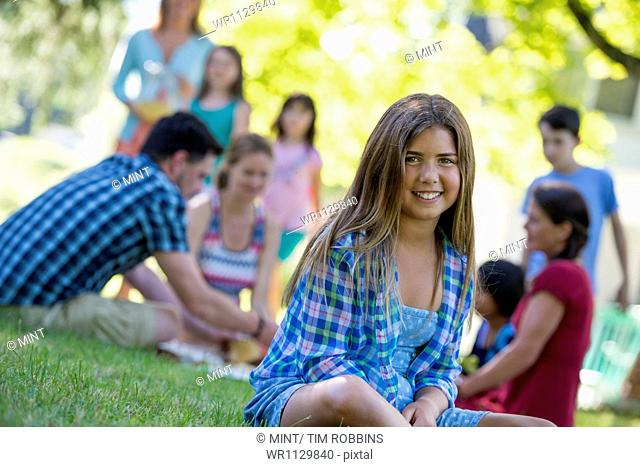 A group of adults and children sitting on the grass under the shade of a tree. A family party