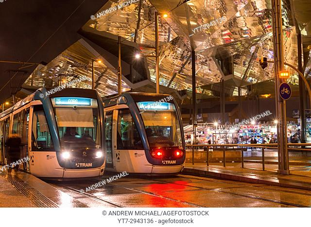 Night view of two trams at Glories station with the dazzling, reflective canopy to the rear. Barcelona, Catalonia, Spain