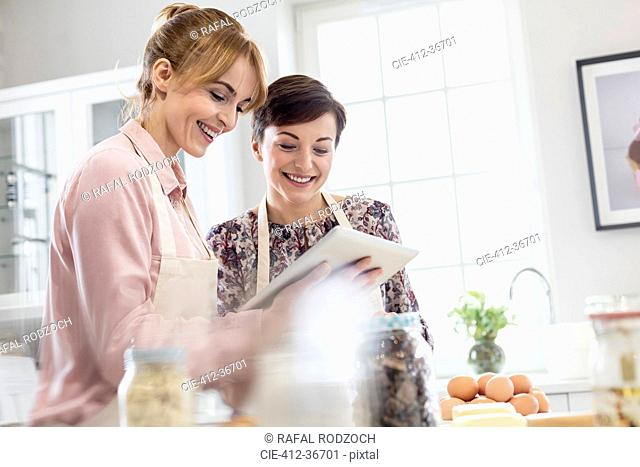 Smiling female caterers using digital tablet, baking in kitchen