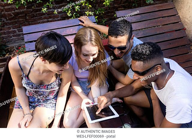 Happy friends sharing tablet outdoors