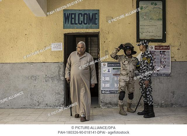 Egyptian military stand guard as a man leaves a polling station on the first day of the 2018 Egyptian presidential elections, in Cairo, Egypt, 26 March 2018