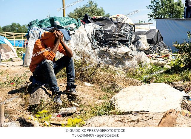 The Jungle, Calais, France. Migrant or illegal immigrant hiding his face to avoid recognition, while sitting on a piece of demolished concrete