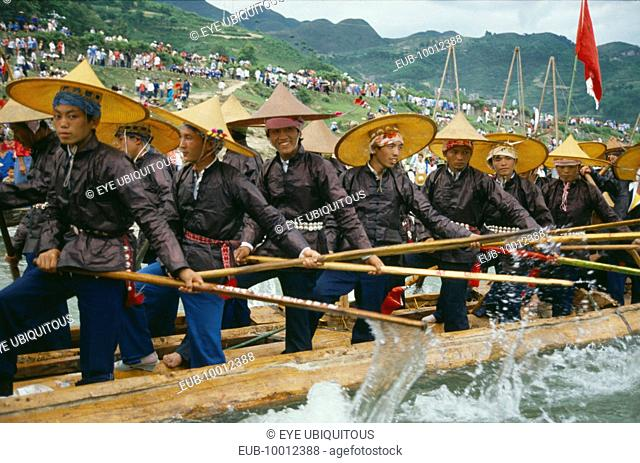 Oarsmen in traditional clothes rowing at dragon boat race