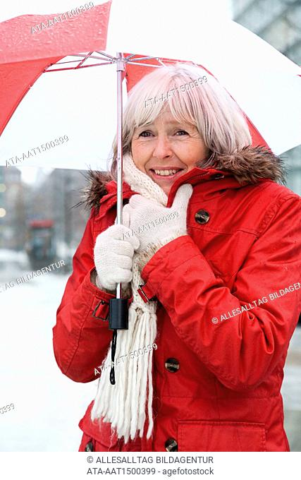 Freezing elderly person with umbrella
