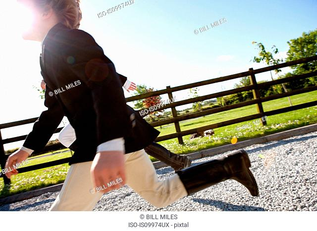 Boys running in horse riding clothes