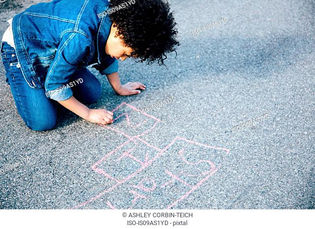 High angle view of girl kneeling using chalk to draw hopscotch game