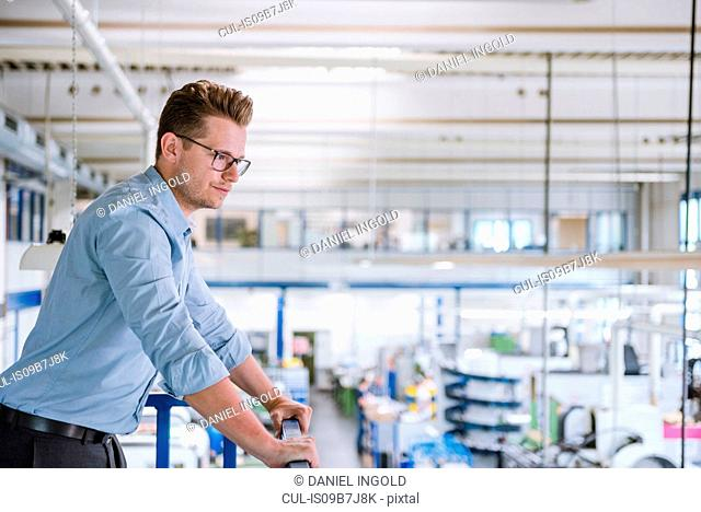 Male manager looking out from factory balcony at production line