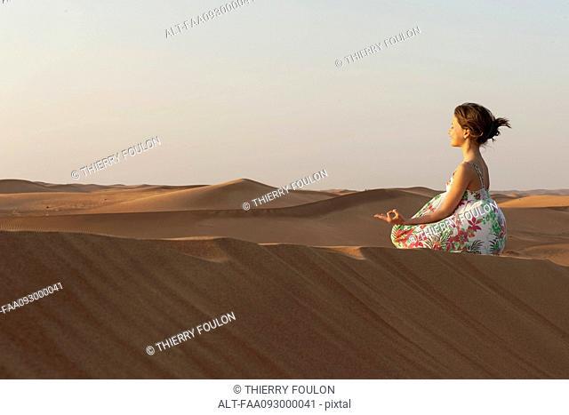 Girl meditating in desert