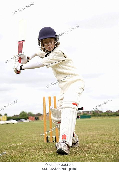 Boy 10-12 playing cricket