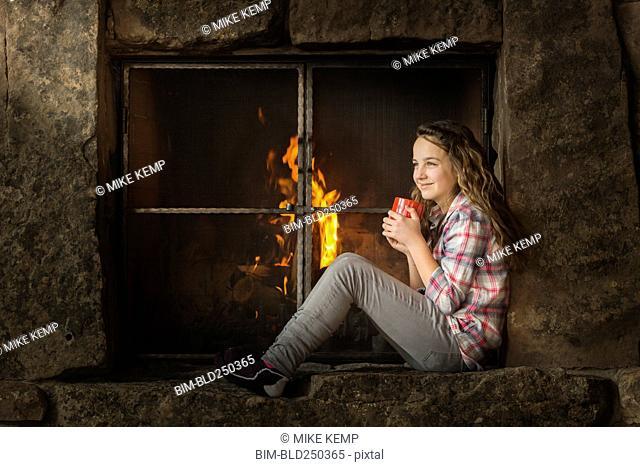 Smiling Caucasian girl sitting near fireplace
