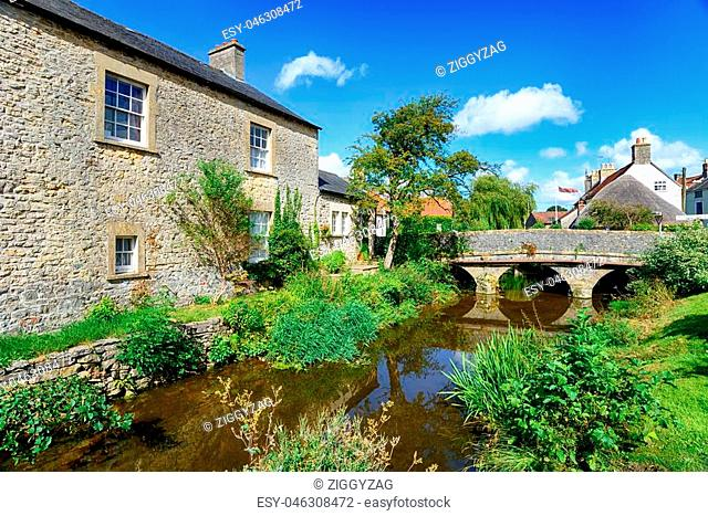Pretty cottages and a bridge over the river at Nunney in Somerset