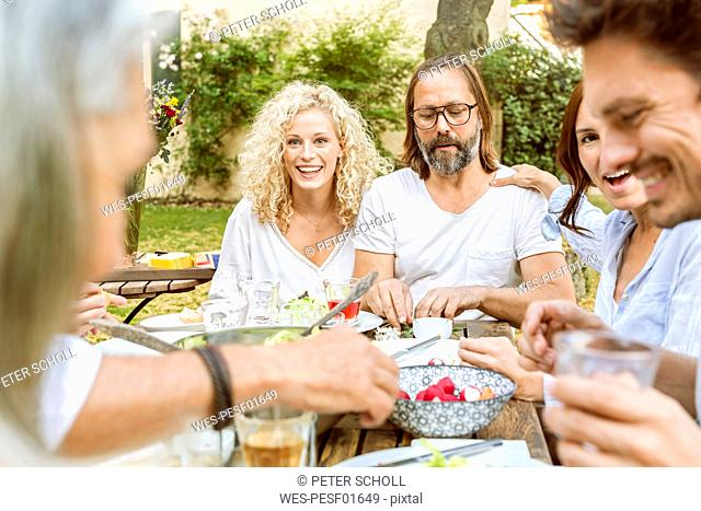 Happy family eating together in the garden