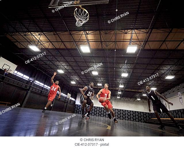 Young male basketball players playing basketball on court in gym