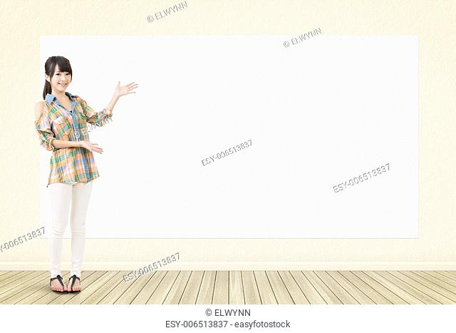 Asian casual smiling woman standing and showing blank white banner, board, placard or poster. Copy-space for advertise