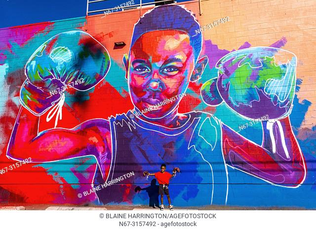 """5 year old Britton Grae-Chapman with boxing gloves in front of a huge mural painted of him by a local artist known as """"""""Detour"""""""" (actual name Thomas Evans)"""