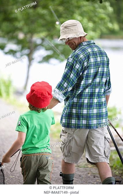 Boy with father going fishing, rear view