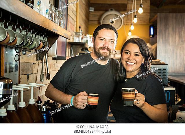 Hispanic couple working in coffee shop