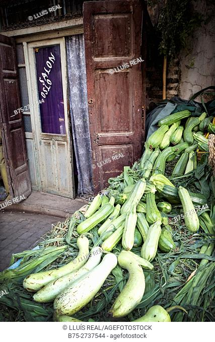 Courgettes in street market, barber shop in background. Fez, Morocco