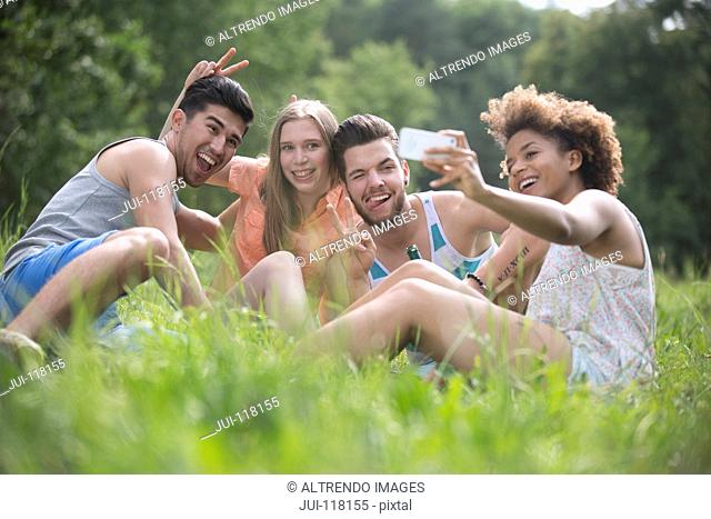 Young Couples Pose For Selfie Sitting On Grass