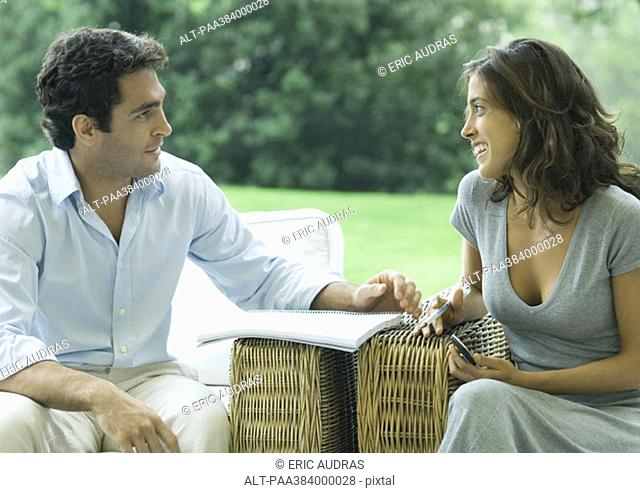 Man and woman sitting in arm chairs outdoors, talking