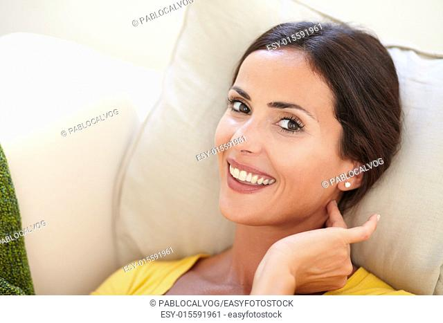 Close up of a relaxed woman toothy smiling at the camera while lying on her back