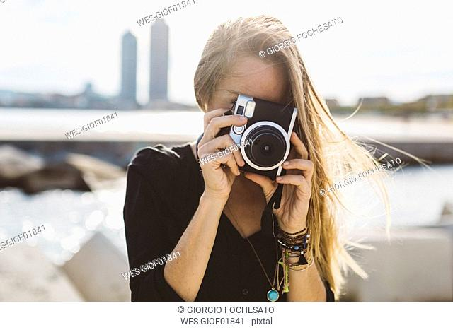 Young woman taking picture with old-fashioned camera at the seafront