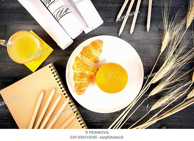 Top view of wooden desktop with orange and croissant on plate, juice, stationery, wheat spikes and paper rolls