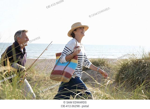 Mature couple with fishing rod walking in sunny beach grass