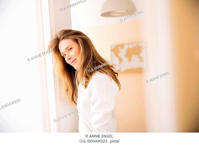 Portrait of mid adult woman leaning against living room doorway