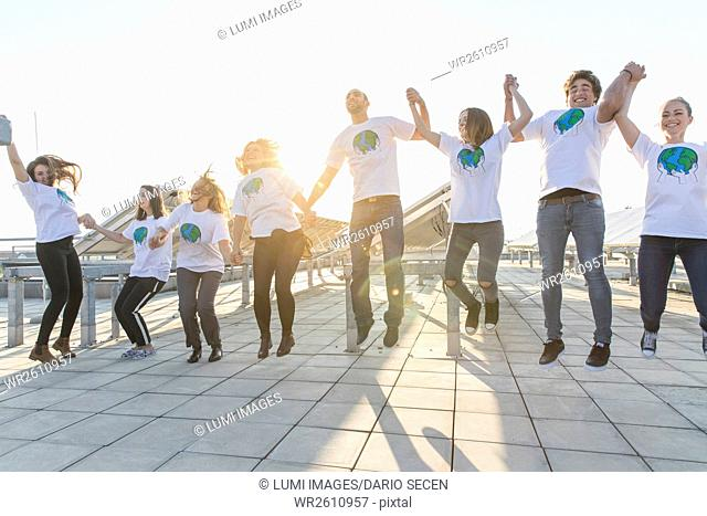 Group of teenage environmentalists jumping and cheering