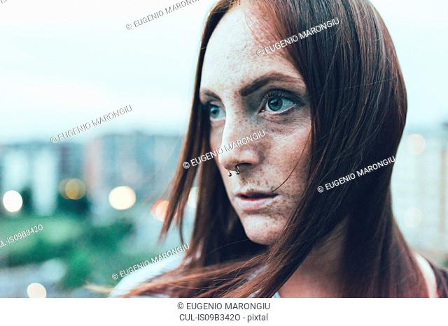 Close up portrait of young freckled woman with long red hair and nose piercing
